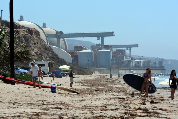 Surfers near the now-shuttered San Onofre reactors in southern California.